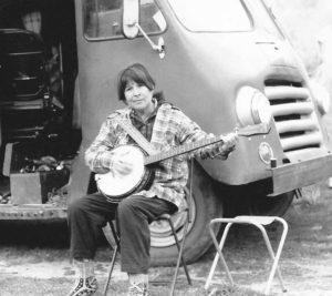 Frances on camp stool plays her banjo, Cleo-May, 1988