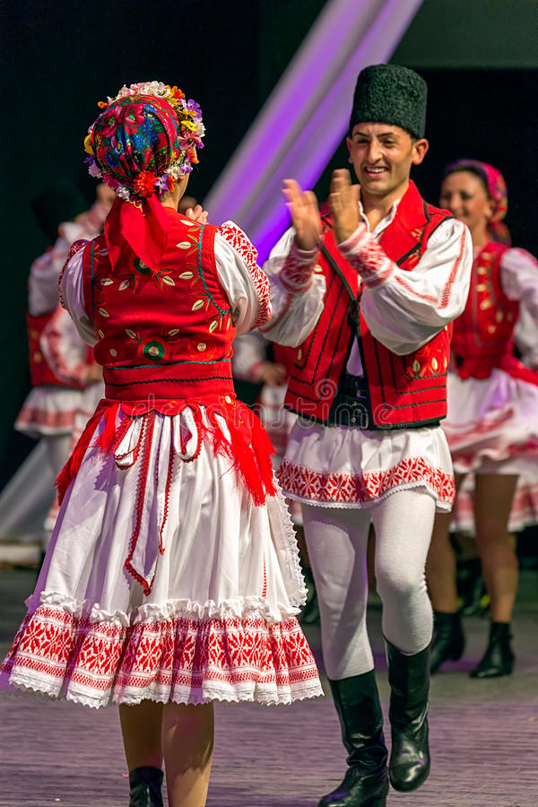 Young couple in Eastern European costumes, dancing