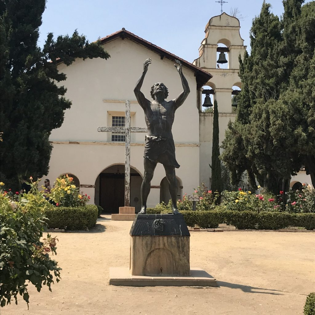 Bronze statue of San Juan Bautista standing before the old mission church