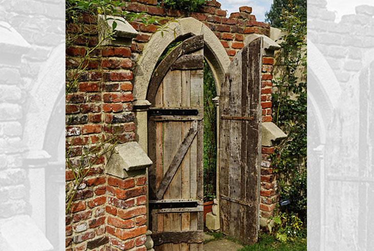 Wooden door ajar in old brick wall