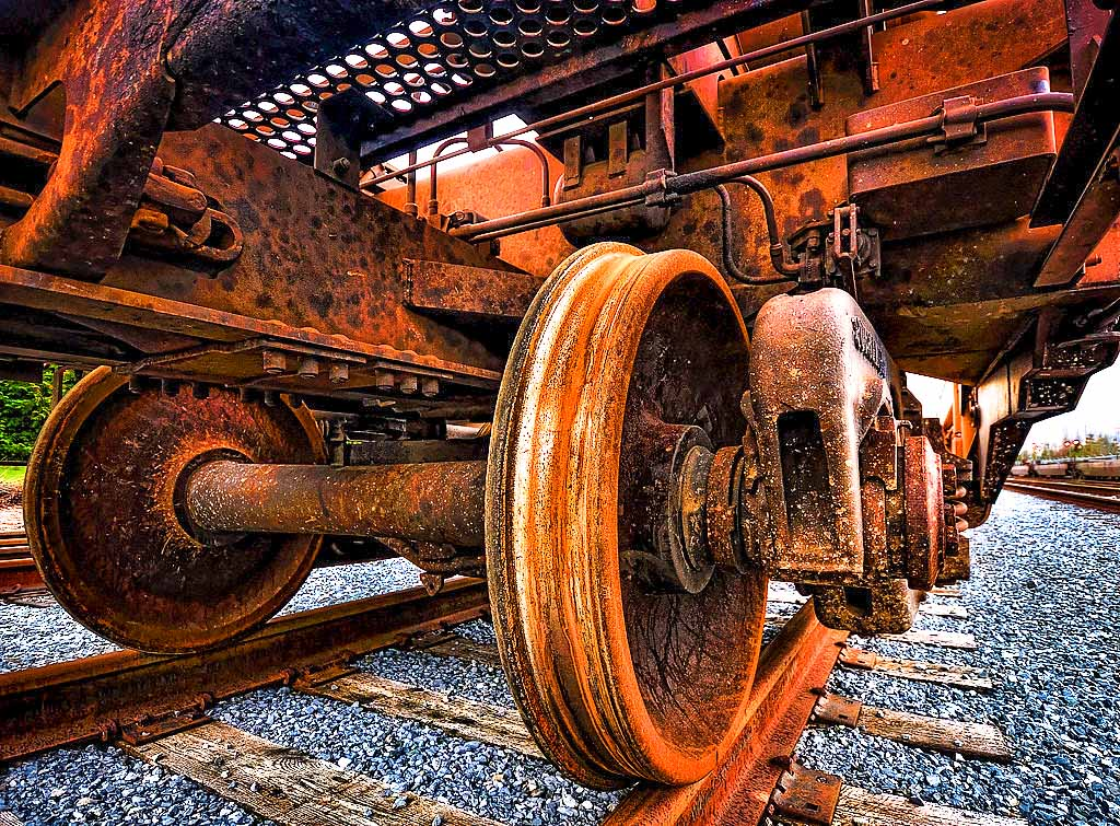 Rusty train wheels on rusty rails. Photo by Gabriel Tompkins.